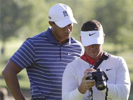 Tiger Woods si s trenérem Seanem Foleym prohlížejí fotky švihu.