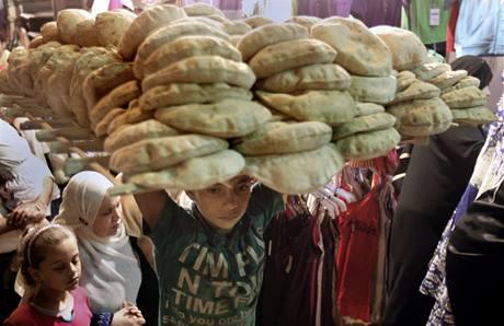 Egyptsk� chlapec nese v K�hi�e t�c s arabsk�m chlebem v p�edve�er sv�tku �d al-fitr