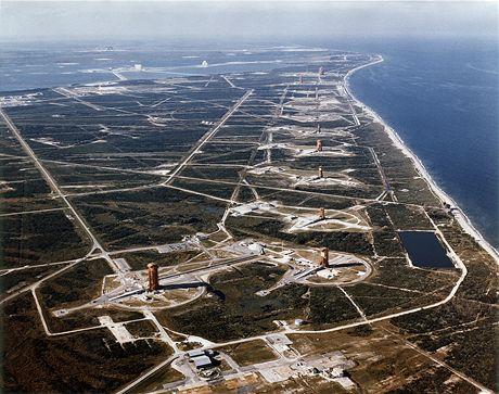 Letecký pohled na řadu ramp vojenské části kosmodromu Cape Canaveral; civilní část Kennedy Space Center je vzadu na obzoru