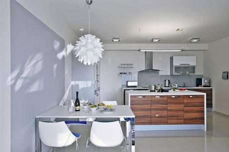 Kuchyni dominuje pracovní ostrůvek, který nahrazuje úložné prostory. V jeho útrobách se skrývají zajímavě řešené zásuvky, které jsou oko návštěvníka zcela skryté.