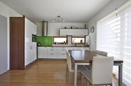 V interiéru dali majitelé přednost dřevu, bílé barvě a střídmým barevným akcentům. V kuchyni vyrobené z bíle lakovaných MDF desek upoutá pozornost obložení stěny zeleným plexisklem.