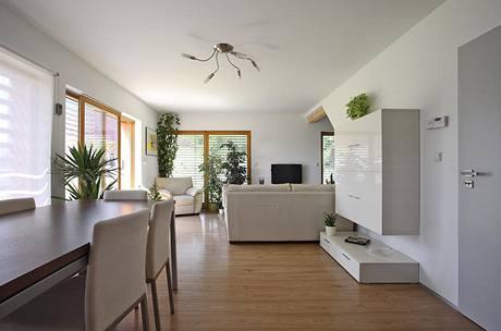 Kromě jídelního stolu a sezení, které je orientováno na západní stranu, není ve společné obytné části mnoho nábytku. Vše se vešlo do bílé skříňové sestavy zavěšené na schodišťové stěně.
