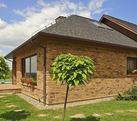 Režná struktura lícového zdiva vytváří dojem masivní stavby, zatímco uvnitř se ukrývá dřevěná konstrukce