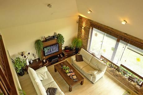 Pohled z galerie. Prostor, kde je umístěno sezení, se otevírá vzhůru do podkroví. Díky nízkým parapetům má obývací pokoj větší kontakt se zahradou a více světla.