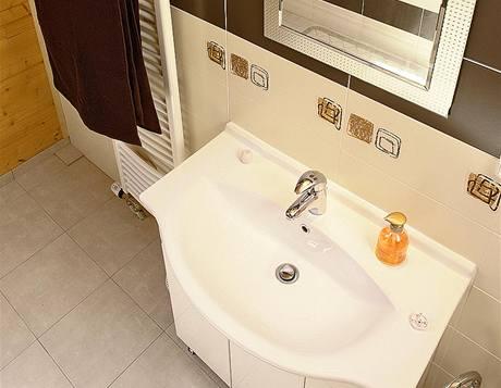 Rodinná koupelna v podkroví v kombinaci dřeva a praktického obkladu