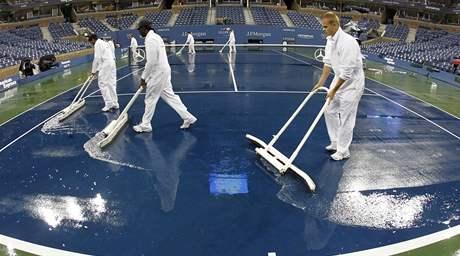 Uklízecí četa stírá vodu ze dvorce Arthura Ashe po dešťové smršti ve finále US Open