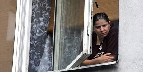 Obyvatelka jednoho z problémových domů v Karviné pozoruje dění před domem, kde začíná kontrola nájemníků.