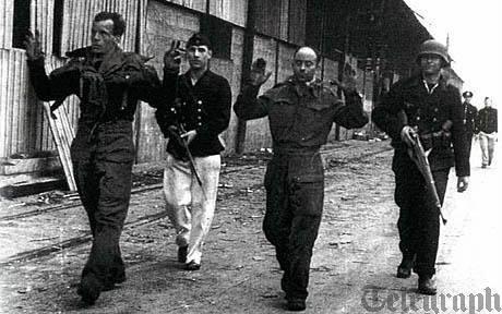 Michael Burn (vlevo) po zajetí v St. Nazaire ukazuje vítězné V.