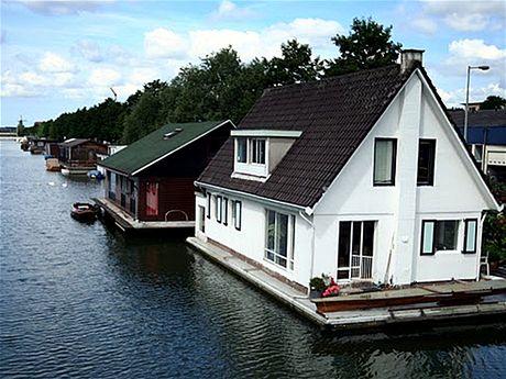 Kousek od nových rezidencí bydlí lidé v plovoucích domech přímo v kanálech, po nichž se dříve plulo k dokům