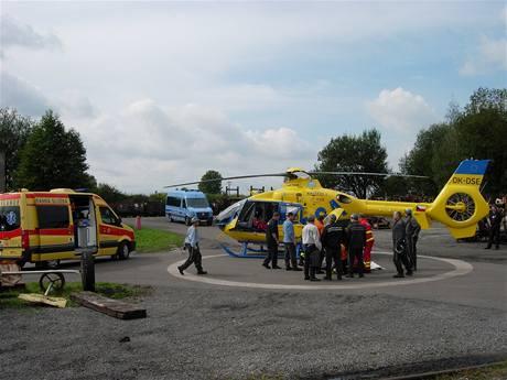 Posádka záchranářského vrtulníku připravuje zraněného horníka k transportu.