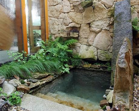 V menším atriu je ochlazovna k sauně. Kameny kolem bazénu obrůstají kapradím, takže téměř nepoznáte, že se nekoupete někde v horách, ale u uměle postavené zdi vyplněné izolací