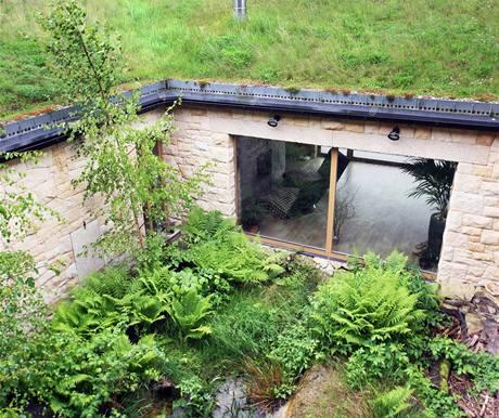 Větší atrium vypadá jako kus lesa. Při pohledu z pavlače za ním místo klasické střechy přízemí vidíte travnatý svah