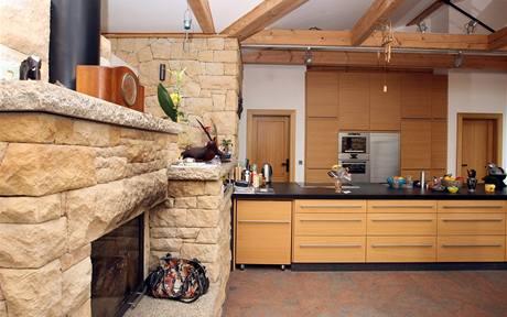 Kombinace kamene a dřeva se odráží i na nábytku. Kuchyňská deska je z černé žuly s hrubým povrchem, který je konzervovaný, aby se na něm netvořily skvrny