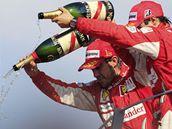 PRŠÍ. Jezdci stáje Ferrari lijí šampaňské z pódia pro vítěze Velké ceny Itálie. Fernando Alonso vyhrál, Felipe Massa byl třetí.