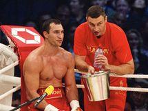 Ukrajinský boxer Vladimír Kličko dostává rady od trenéra v zápase proti Nigerijci Peterovi v zápase o mistrovský titul organizací WBO a IBF.