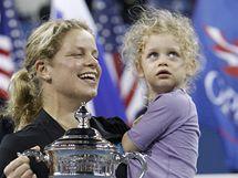 Tenistka Kim Clijstersová drží v jedné ruce trofej pro vítězku US Open, ve druhé svou dceru Jadu.