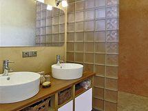 Koupelna je zajímavou kombinací keramické dlažby, benátského štuku, přírodního dřeva a skla. Podlahu ve sprše pokrývá mozaika.