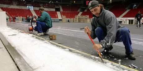 Dělníci ostraňují zbytky ledu pod odmontovanými mantinely při přípravě plochy karlovarské KV Areně pro basketbalové MS žen (25.9.2010)