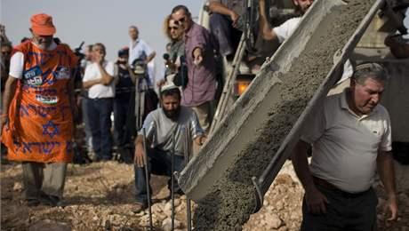 """Židovští osadníci během slavnostního """"pokládání základního kamene"""" další stavby v osadě Kirjat Netafim (26. září 2010)"""