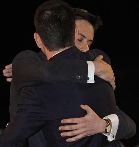 David Miliband (zády) gratuluje svému bratrovi Edovi ke zvolení předsedou labouristů.