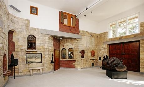 Nepravidelně členěnému interiéru dominuje vysoký ateliér jako přirozené pracovní a duchovní středisko stavby