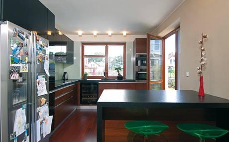 Kuchyně ve tvaru písmene L je na návrh architektky obložena sklem