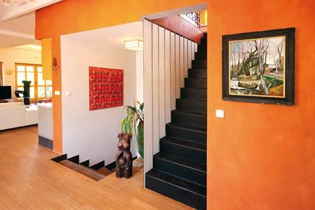 Výrazně barevná stěna rámuje vstup na schodiště