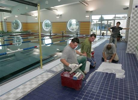 Řemeslníci dokončují dlažbu v hale krytého bazénu v Zábřehu.