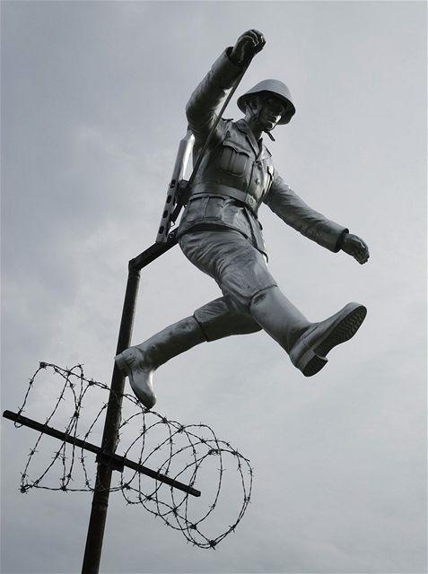 Socha skákajícího východoněmeckého pohraničníka Conrada Schumanna v berlínské ulici Bernauer strasse.