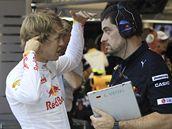 Sebastian Vettel (vlevo) řeší před tréninkem problém s mechanikem Red Bullu.