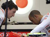 Lewis Hamilton prohlíží s mechanikem McLarenu monopost.