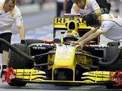 Robert Kubica a jeho monopost v péči mechaniků stáje Renault.