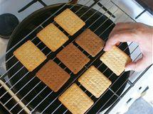 V pánvi přiveďte k varu trochu vody, na ni položte mřížku na chladnutí moučníků a na ni rozložte sušenky