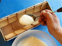 Přibližně třetinu náplně nalijte na dno formy vyložené sušenkami a vrstvu uhlaďte