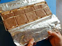 Navrch nalijte zbytek krému, zaklopte ho sušenkami, naplněnou formu zabalte do fólie a nechte v chladničce ztuhnout