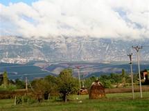 Albánie. Hrozivá hradba hor – po levé straně se uprostřed masivu rýsuje zástavba města Krujë