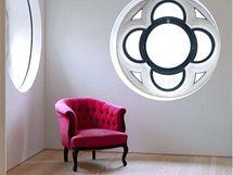 Pohled z postele na čtenářský koutek v rohu ložnice. Klidná bílá barva je narušena jen nachem pohodlného křesílka a rozetovými okny