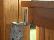 Dřevěný altán je otevřený pohledům do zahrady přes dřevěné ohrazení, které lze ale snadno odstranit. Stačí jednotlivá pole nadzdvihnout, vysadit po obou stranách z ocelových čepů a pavilon je hned volně přístupný ze tří stran
