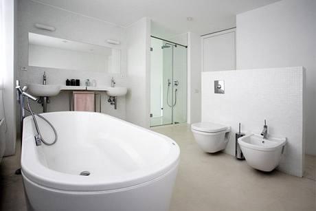 """Italská sanitární keramika oválných tvarů, chromované sifóny a """"trubkové"""" baterie designéra Rona Arada navozují v rodinné koupelně atmosféru třicátých let. Strukturovaná"""