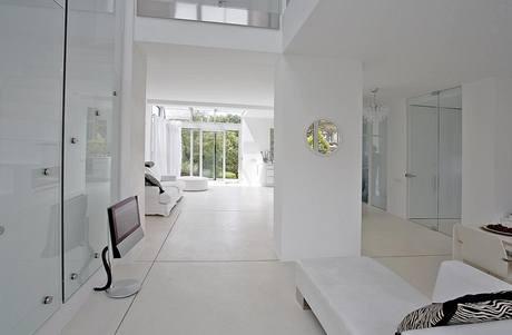 Otevřené přízemí, tonoucí v bílé barvě, nabízí volné průhledy (a volný průchod denního světla a energie) všemi směry. Pro majitelku je důležité, že každé místo má optický kontakt se zahradou.