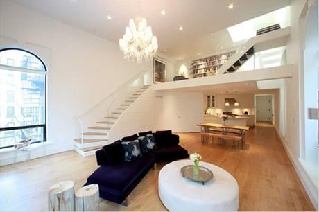 Pohled z rohu obývacího pokoje až k vchodovým dveřím. Na relaxační zonu navazují jídelní lavice a kuchyň
