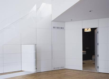 Rafinovaný úložný prostor po schodištěm se skleněným zábradlím. Pod schody se podařilo kromě technického zázemí zakomponovat i vinotéku, moderní audio sestavu a malou toaletu pro hosty