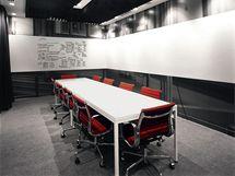 Konferenční místnost. Tabulový pruh podél celé místnosti je z praktického hlediska neocenitelný. Šedé tóny a kov doplňuje červeň židlí Eames od Vitry