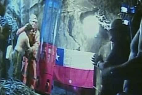 Zavalení horníci vítají záchranáře, který se k nim spustil speciální záchrannou kabinou (13. října 2010)