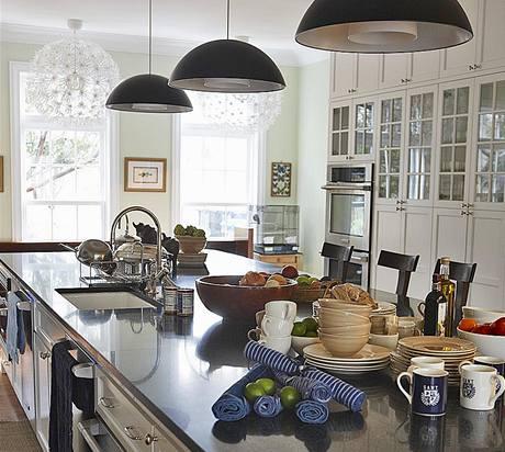 V tradičně uspořádané kuchyni se snoubí masivní dřevěný nábytek, zdobený stylizovanými dobovými detaily (rámová dvířka, kovové úchytky, fasetové skleněné výplně) a technicky vyspělá svítidla s moderním designem