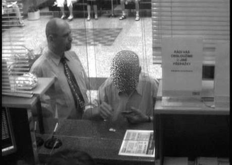 Podvodník přihlíží, jak oklamaný důchodce vybírá v bance peníze.