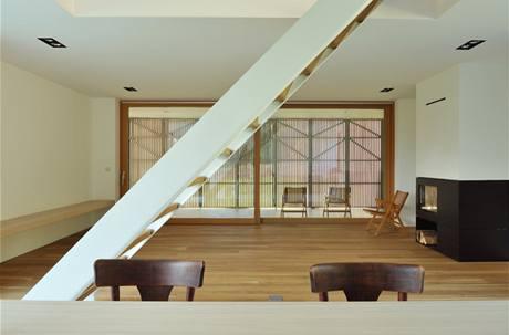 Pohled z interiéru. Okenice jsou zavřené. Terasa je součástí domu, posuvné panely kopírují její vnější stranu