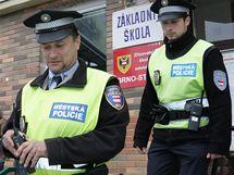 Brněnští strážníci opouštějí volební místnost na Základní škole Hroznová v Brně-Pisárkách. (15. říjen 2010)