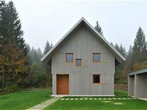 Pohled na dům od přístupové cesty. Otevřené panely odhalují medově modřínová okna a dveře