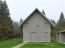 Pohled na dům od přístupové cesty. Uzavřený dům působí monoliticky a nepřístupně